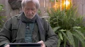vállkendő : Elderly senior man in his 70s reacting to his digital tablet shaking his head yes and no enjoying his leisure time
