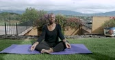 flor cabeça : Healthy African American senior in 60s sitting cross legged meditating outside on a yoga mat - dolly shot Stock Footage
