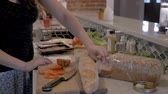 pronto para comer : Healthy, fit woman making a sandwich for lunch with healthy fresh vegetables, cold cuts, meats, and sliced bread - slow motion dolly shot Stock Footage