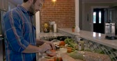 pijama : Push in of a handsome man putting sliced tomatoes and lettuce on a turkey and roast beef sandwich Stock Footage