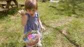 április : Adorable 2 - 3 year old girl in spring dress holding an easter basket filled with easter eggs in slow motion