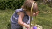 április : Beautiful young innocent 2 - 3 year old girl looking at her Easter basket in slow motion