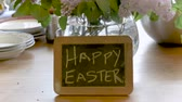 wazon : Happy Easter written on a small chalk board against a vase of pretty flowers on a wooden table as part of a Easter brunch- push in Wideo