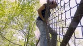 perseguição : Low angle of a man carefully climbing over a chainlink fence breaking into private property in slow motion Stock Footage