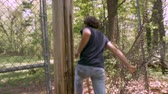 perseguição : Man being chased breaks through a chain link fence and runs in the woods Stock Footage