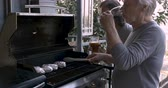 alumínio : A man with long hair cheers an elderly man in his 70s grilling on a barbecue with drink