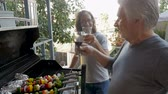saúde : Older father and son grilling vegetable kebabs on a gas bbq grill cheering with beer and wine spending quality time together in slow motion
