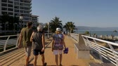 mexicano : PUERTO VALLARTA, MEXICO - CIRCA MARCH 2018 - Camera following tourists walking on the Rio Cuale bridge on the Malecon in slow motion Stock Footage