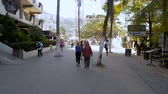 farmers market : PUERTO VALLARTA, MEXICO - CIRCA MARCH 2018 - People walking towards Olas Altas Saturday Market in Old Town in the Romantic zone - slow motion