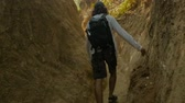 vezetett : Man wearing a daypack backpack walking and hiking through a narrow path touching the rocky wall with his finger in slow motion