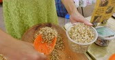 plântula : Woman scooping sprouted lentils into a plastic container at a farmers market and getting them ready for sale