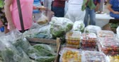 rúcula : Shopper buying and selecting fresh organic greens, lettuce, cherry tomatoes, and arugula in plastic bags and containers at a farmers market