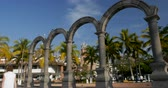 puerto vallarta : PUERTO VALLARTA, MEXICO - CIRCA MARCH 2018 - Tourists walking by the arches at the Plaza de Armas on the Malecon and a view of the church of our lady Guadalupe