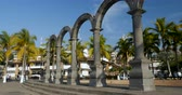 puerto vallarta : PUERTO VALLARTA, MEXICO - CIRCA MARCH 2018 - people walking next to the The arches and plaza de armas along the Malecon with a view of the crown of the church of our lady Guadalupe during the day