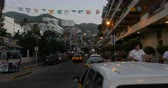 ült : PUERTO VALLARTA, MEXICO - CIRCA MARCH 2018 - Active city life with workers and tourists on Olas Altas Street looking towards the condos and the mountains - dolly shot Stock mozgókép