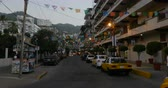 ült : PUERTO VALLARTA, MEXICO - CIRCA MARCH 2018 - Banners, taxi cabs, and people at dusk on Olas Altas Street looking towards the condos and the mountains