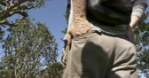 cep : Low angle of a man with his hands in his back pockets of his cargo pants outside in a park setting Stok Video