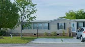 laje : Establishing shot of a manufactured home with an SUV car in the driveway and a couple of trees with green leaves during the day - dolly shot