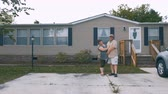 szerény : Portrait of a happy heavy couple hugging in front of a manufactured home and looking at the camera smiling - wide shot Stock mozgókép