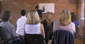 apresentador : Attractive multi-ethnic businesswoman writing growth on a white board at a seminar or business meeting while the audience cheers and applauds - dolly shot Vídeos
