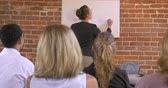 apresentador : Audience applauding at a business presentation when a woman is writing on white board - dolly shot