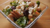 feta : Push in of a healthy vegetarian kale, pecan nut, garbanzo, cranberry and cheese salad in a square glass bowl