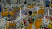 TZURUMUTARO, MEXICO - NOVEMBER 1, 2016 - Crane up of a teenage boy preparing a grave with flowers and candles for day of the dead