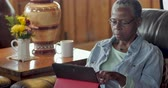 видя : Attractive healthy, elderly senior black woman in her 50s or 60s using her digital tablet in her living room while sitting on the sofa