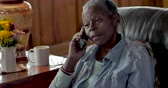 bothered : Frustrated, mad, senior black woman in her 50s or 60s talking on her mobile phone displeased at the annoying caller on the other end