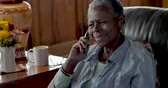 answering : Happy smiling elderly senior black woman in her 50s or 60s answering and talking on a flip phone telephone in her modern home