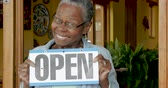 comerciantes : Excited black woman holding her open sign in front of her new business anticipating her new customers
