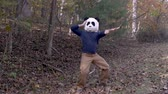 間抜けな : Man wearing a panda head mask dancing and celebrating like hes a winner outside in a park - slow motion
