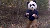 viral video : Man silly dancing and celebrating with a panda head mask while outside in a park - slow motion
