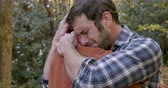 bothered : Upset sad man hugging a woman after getting bad news or mourning the loss of someone while outdoors at a park Stock Footage