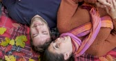 intimität : Young beautiful couple laughing, smiling and in love lying on a blanket with fall leaves - overhead shot