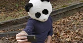 панда : Man wearing a panda head mask taking photos of himself with a mobile phone and nodding yes after looking at the photographs