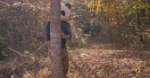 bizarro : Man wearing a panda head mask peaking from behind a tree in a park or forest during the day