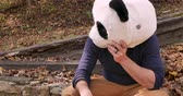 панда : Man wearing a panda head mask acting sad and crying while sitting outside in a park Стоковые видеозаписи