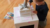 brinquedos : An adorable toddler boy coloring and playing with a robot suit made from cardboard boxes