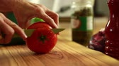 фета : a woman prepares a tomato for a delicious greek salad for dinner