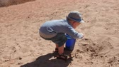sandálias : A little boy plays in a sandy beach on the bank of the Green River near Moab utah Stock Footage