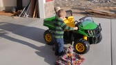 bebês : A little boy uncovers an electric truck on the driveway for his birthday