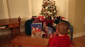 noel kartı : a little boy looking at his christmas presents under the tree Stok Video