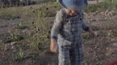 bebês : a toddler is trying to use a shovel outside his house Stock Footage