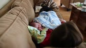 new house : a tired mother takes a quick nap with her newborn baby boy Stock Footage