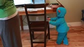 casa : a mother working from home in her home office with her toddler boy playing in a monster costume