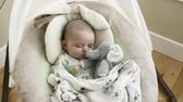 sen : A newborn little boy sleeping in a swing
