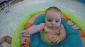 yüzme : A tiny baby boy floating in the swimming pool with family