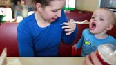 babeczka : a family sitting in a booth at a fast food restaurant eating food