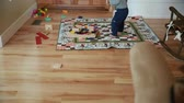 brinquedos : a little boy playing with his toys in the living room jib shot